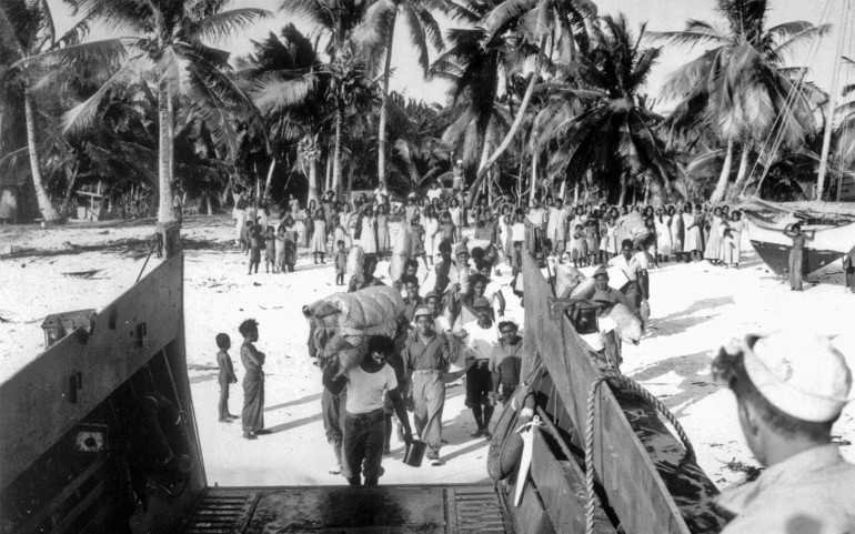 "FOR USE WITH FEATURE PACKAGE FOR MONDAY, JULY 15--FILE--An advance team of Bikini men board a landing craft to assist U.S. Navy Seabees in building new homes for the islanders on Rongerik. The Bikinians had to evacuate their island before ""Operation Crossroads,"" the U.S. military's nuclear test blasts at Bikini atoll in July, 1946. (AP Photo/file)"