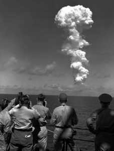 Americans scientists, journalists, and soldiers, watch the explosions from far away.